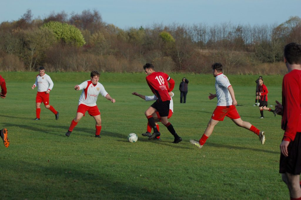 Ryan Armstrong faces a trio of challengers for the ball.