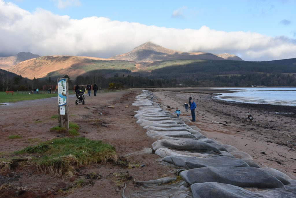 Brodick beach with its exposed geotextile sandbags and weathered beach still attracts a number of families and walkers.