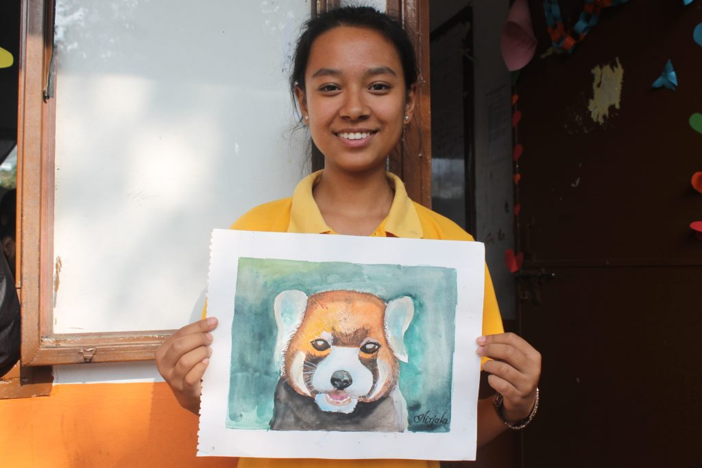 Nirjala with one of her paintings.