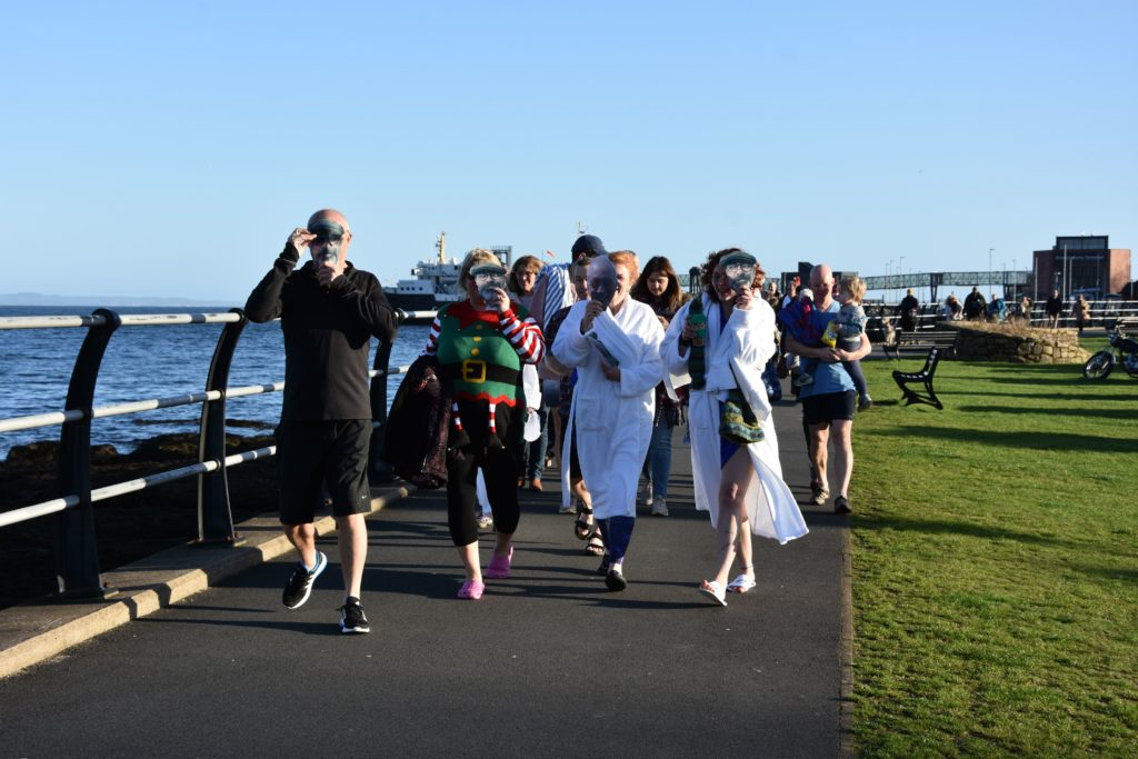 The participants at the head of the procession make their way along the promenade with face masks in honour of friends who could not make the dook this year.