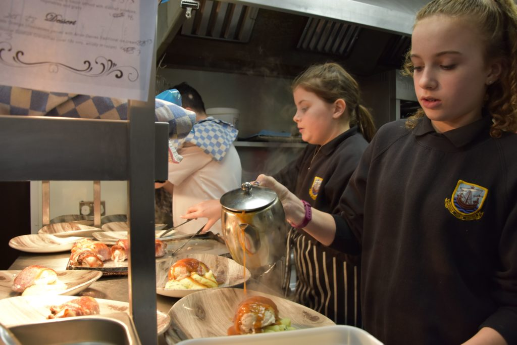 Youth group members work in tandem to plate up the main course.