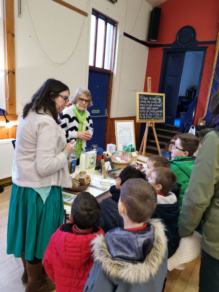 Children listen eagerly to Val Waite who describes methods of sustainable practise at the Eco Savvy stall.