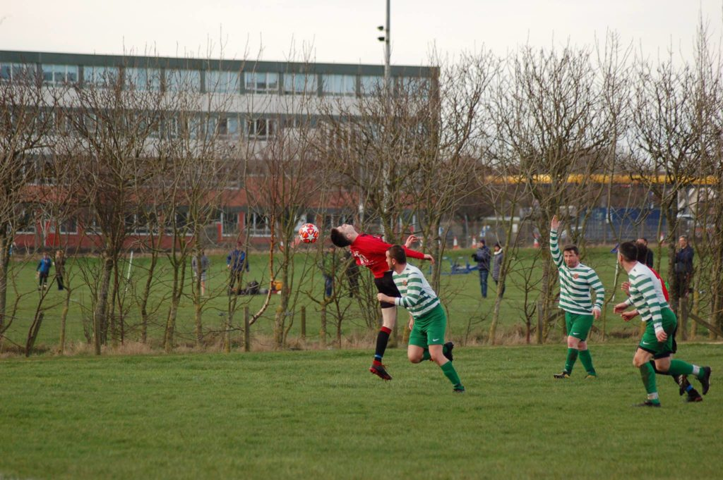 An Arran player contorts himself to pass on possession of the ball.
