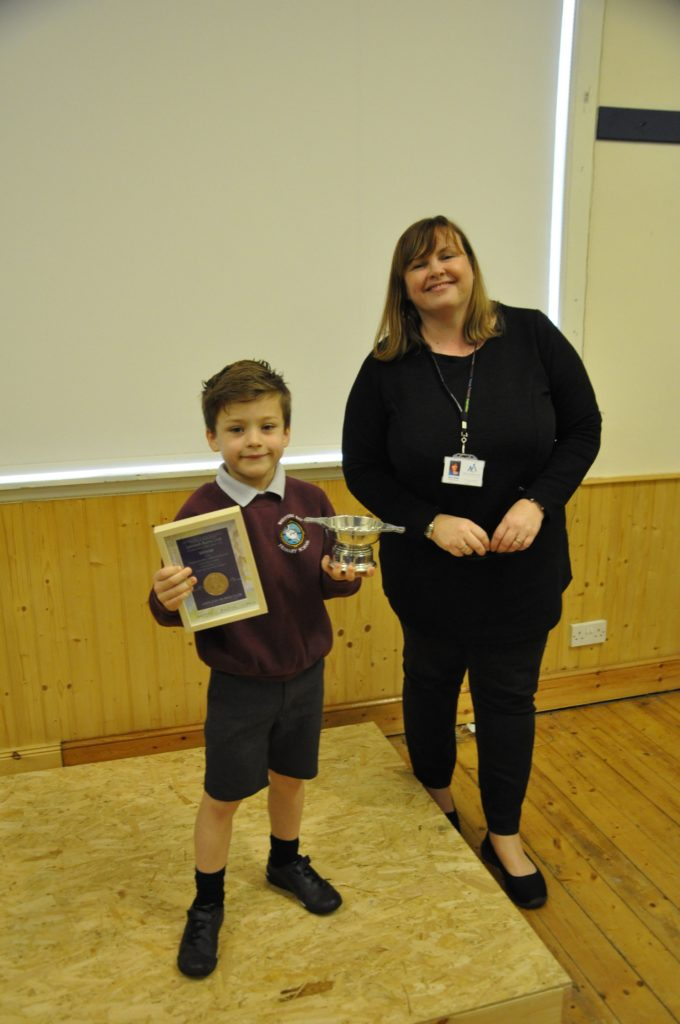 Adjudicator Gillian Seaman presents Louis Henbery with a Quaich for winning the primary 1 and 2 category of the Burns poetry competition.
