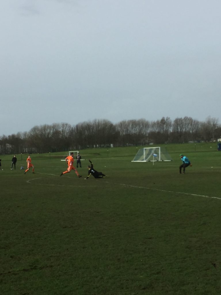 A Hip Flask player slides in front of an Arran striker who bears down on the opposition goalkeeper.