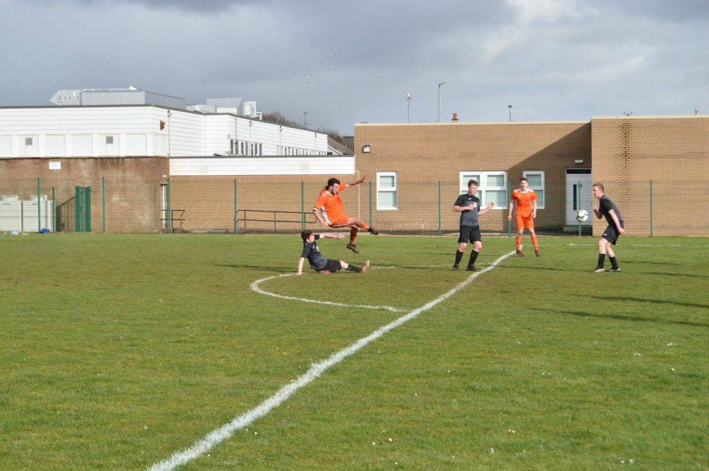 Players narrowly avoid crashing into each other as they both struggle for the ball.