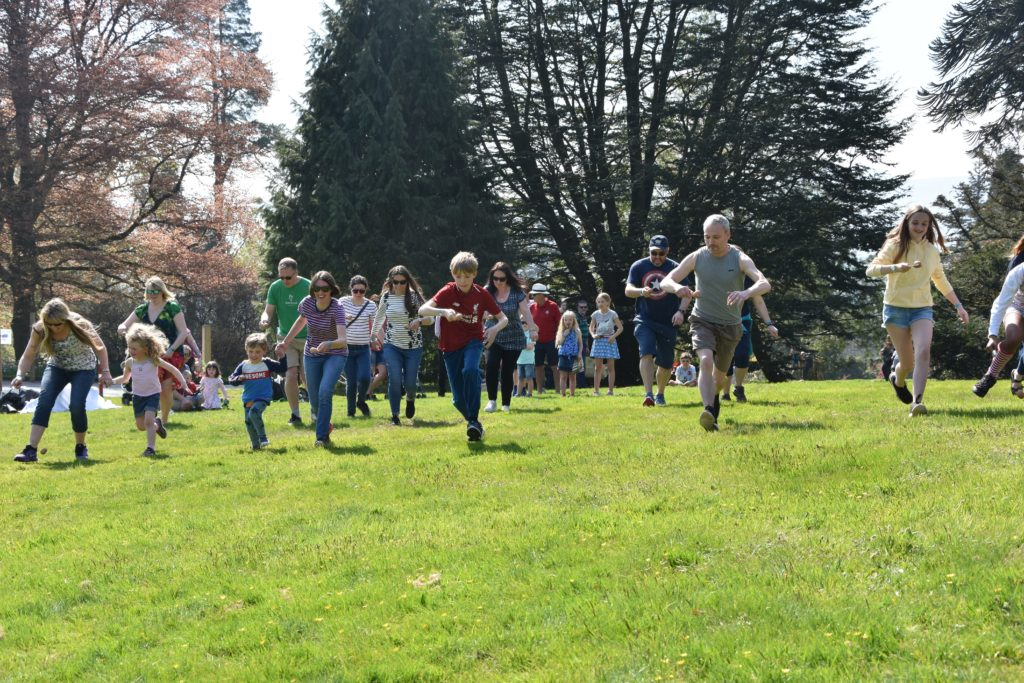 Adults join in on the fun of the egg and spoon race.