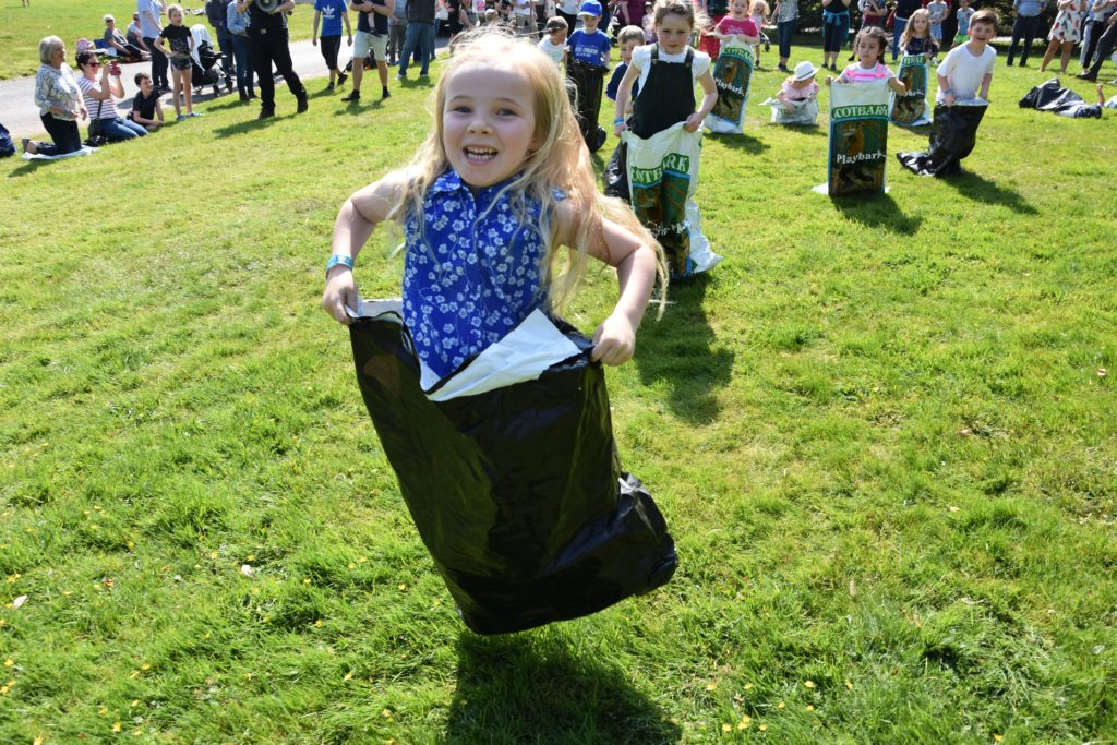 A smiling young girl leads the pack in the sack races.
