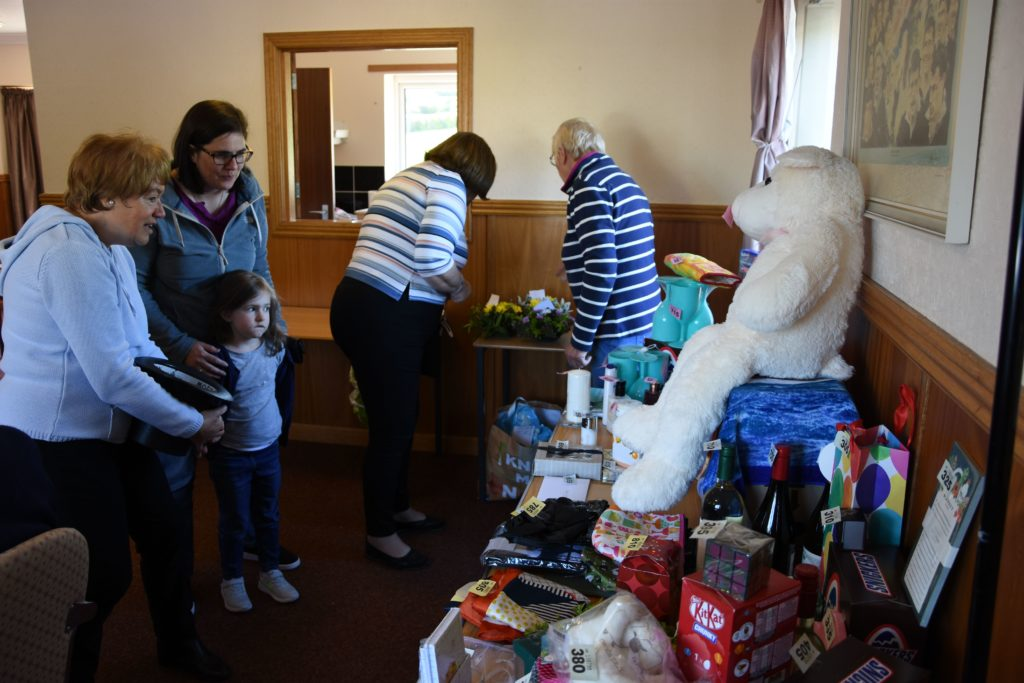A young girl and her mum pick their favourite items before buying tombola tickets from volunteer Elaine Duncan.