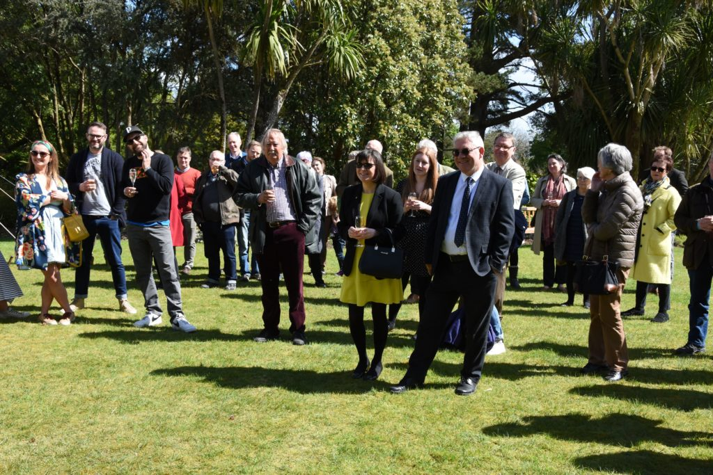Visitors and invited guests enjoy the spring sunshine in the manicured gardens.