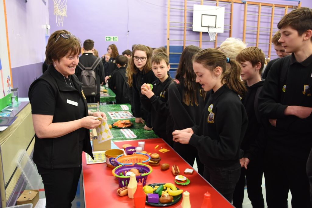 Ayrshire and Arran project coordinator for RHET, Elaine Bryson, watches on as pupils assemble plastic food items.