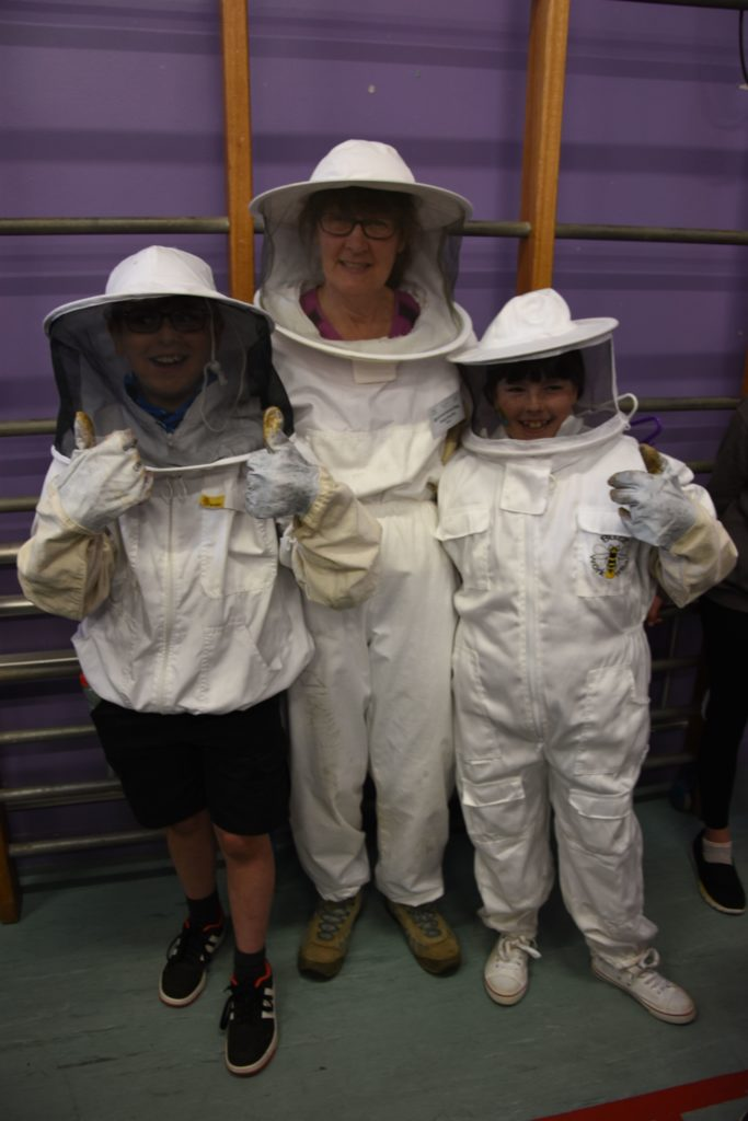 Pupils try on a beekeepers suit with Arran beekeeper Margo McLellan.
