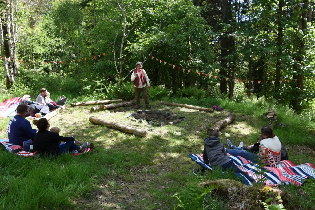 Relaxing in the shade in the forest, children listen to the captivating storytelling from Marty Ross of Whiting Bay.