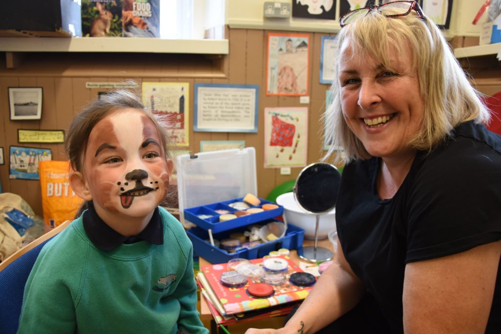 Hayley Carey is pleased with her face painting done by Julie Hunter.