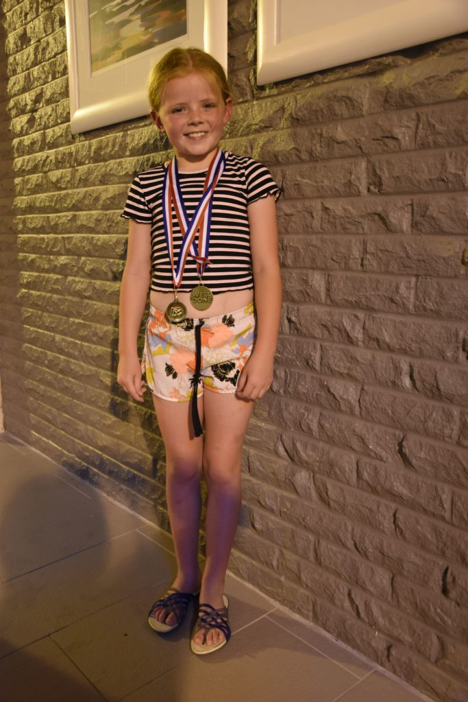 Isla McKinnon shows off her medal haul.