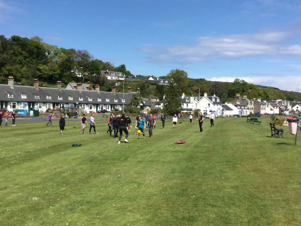 Out in the sunshine, pupils enjoy a football game on Lamlash Green.