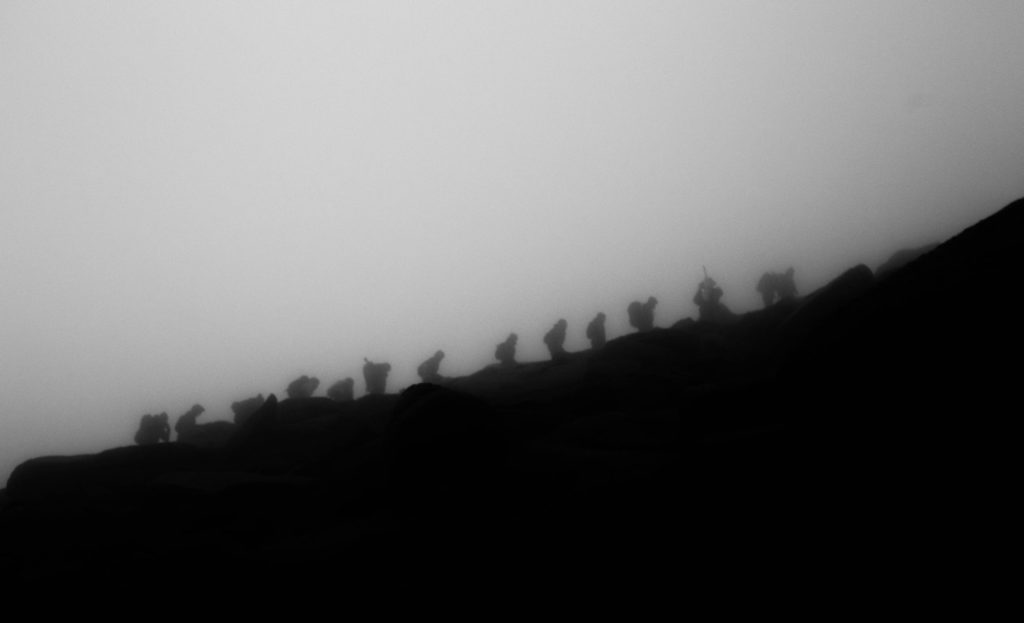 Silhouetted by the darkness, walkers make their way up the Goatfell path.
