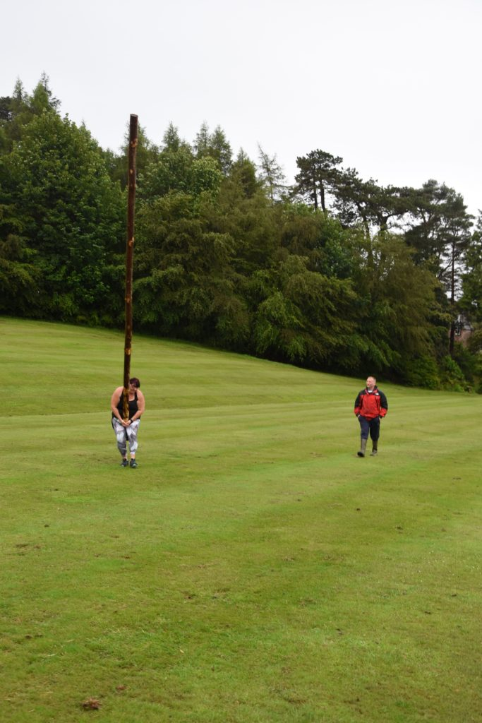 Yvonne practices tossing the caber under the watchful eye of Scott Clark.