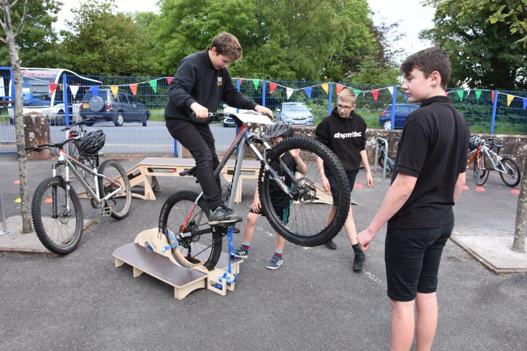 An Arran High School Mountain Bike Club member demonstrates how the Manual Master machine works.