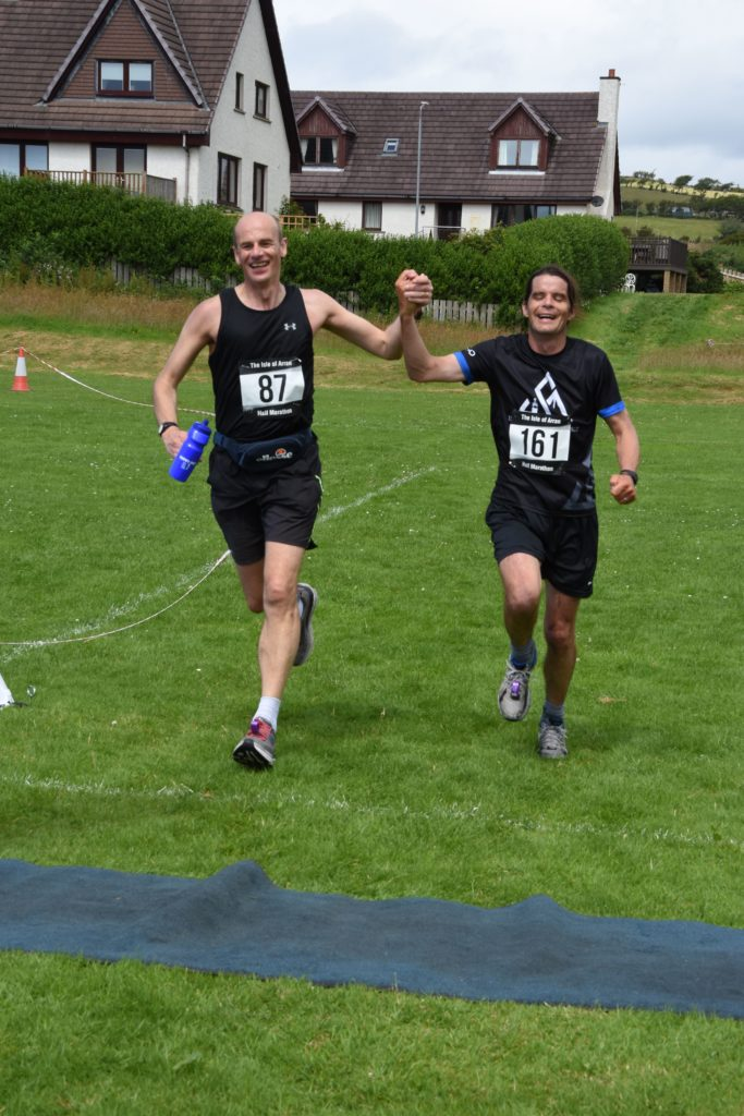 Neil Miller and Andy McNamara laugh and hold hands as they cross the finish line.