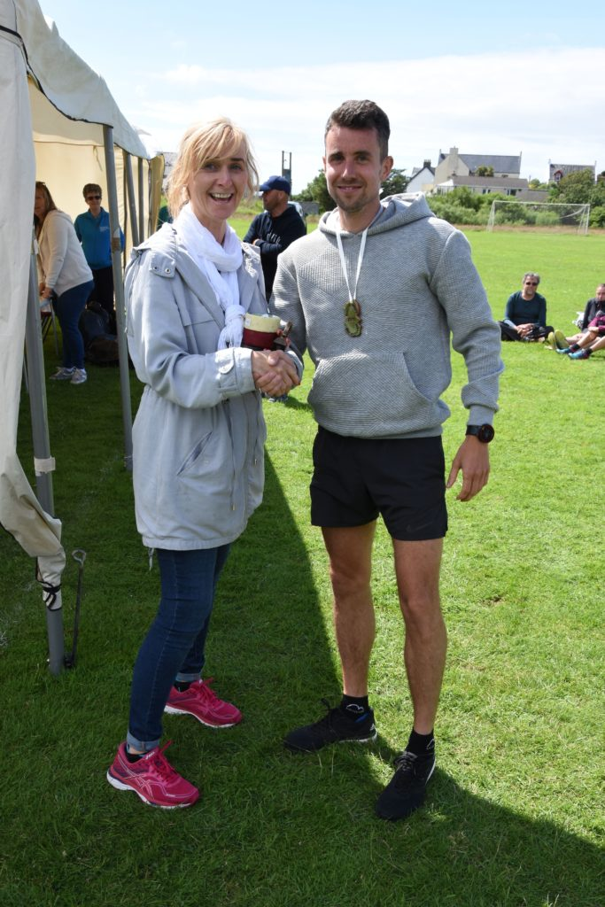 Barbara Crawford present race winner Gregor Yates with his trophy.