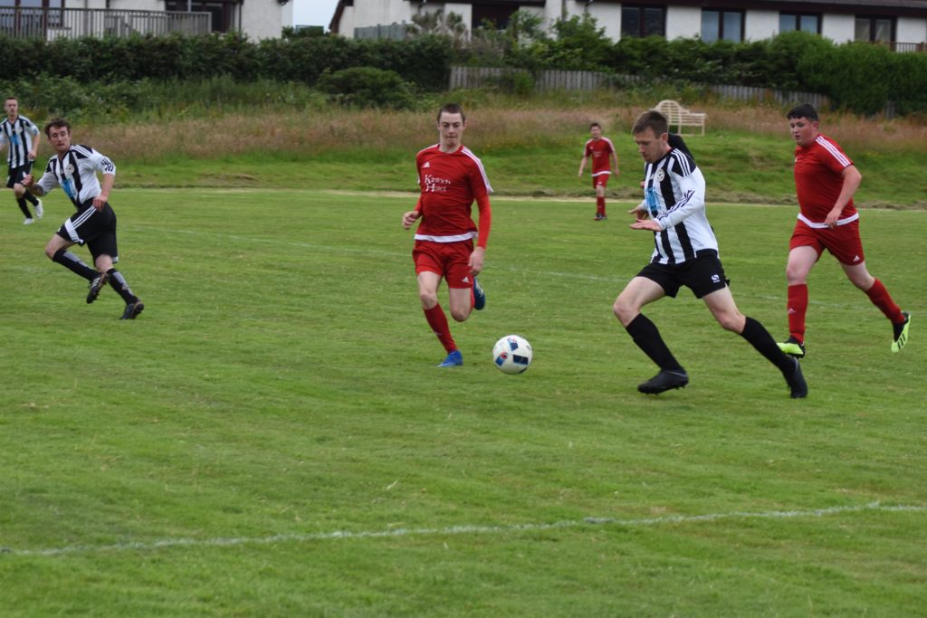 Goal scorer Ben Tattersfield powers down the sideline with Shiskine players in hot pursuit.