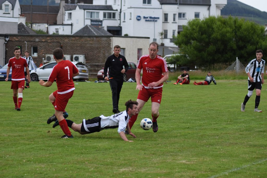 Johnny Sloss trips in a tackle under the watchful eye of referee Danny Head.