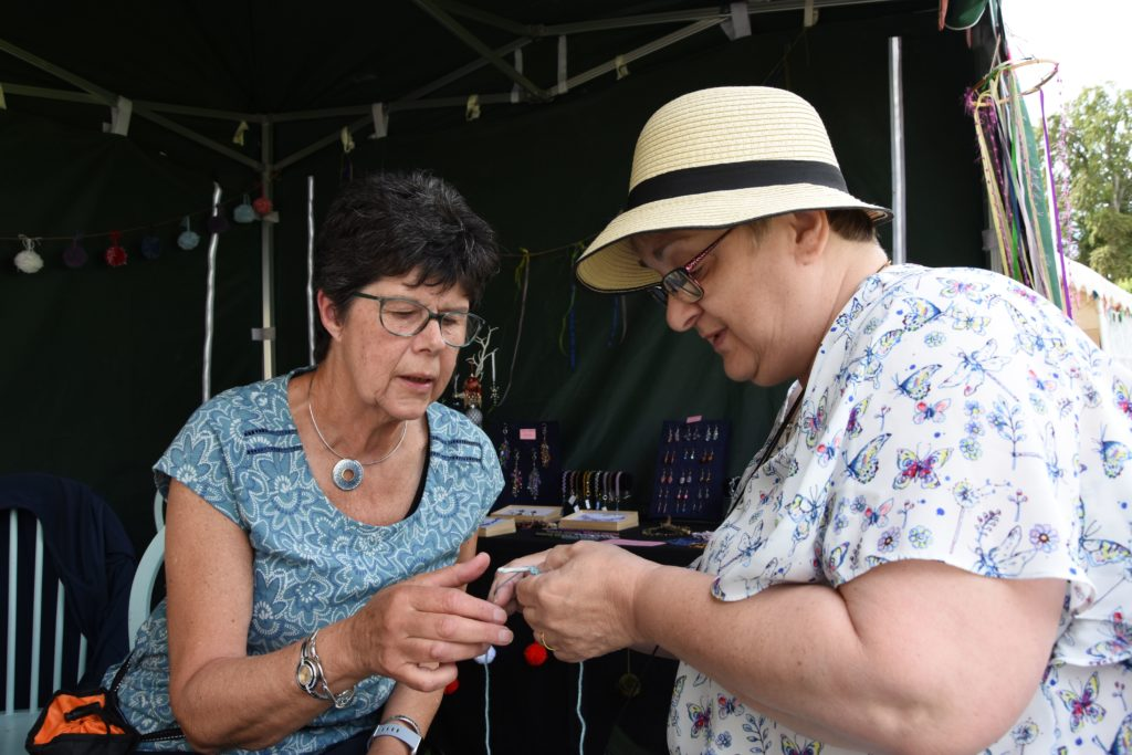 Jenny Clutterbuck teaches Carol Quinney how to crochet during a crochet workshop.
