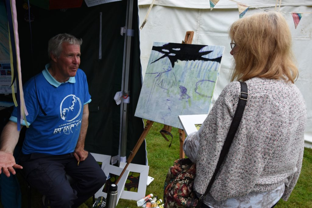 Artist Gordon Davidson speaks with a visitor about his art and the charity that it supports.