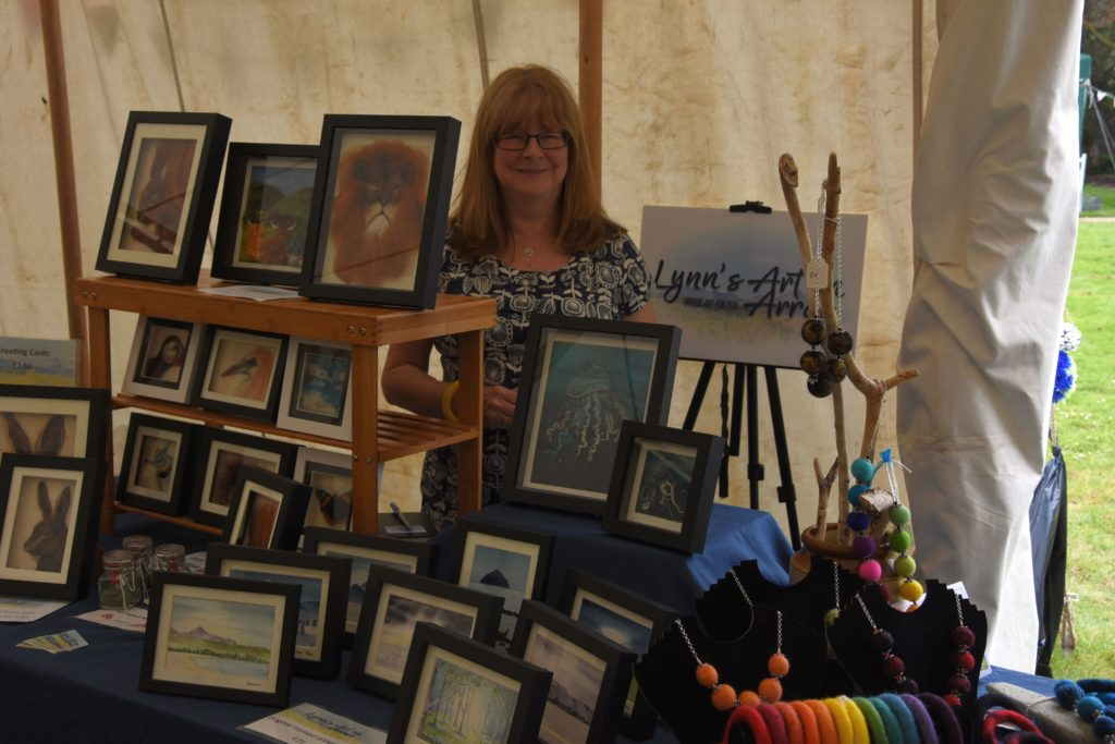 Lynn Jones of Lynne's Art on Arran stands among some of her favourite works.