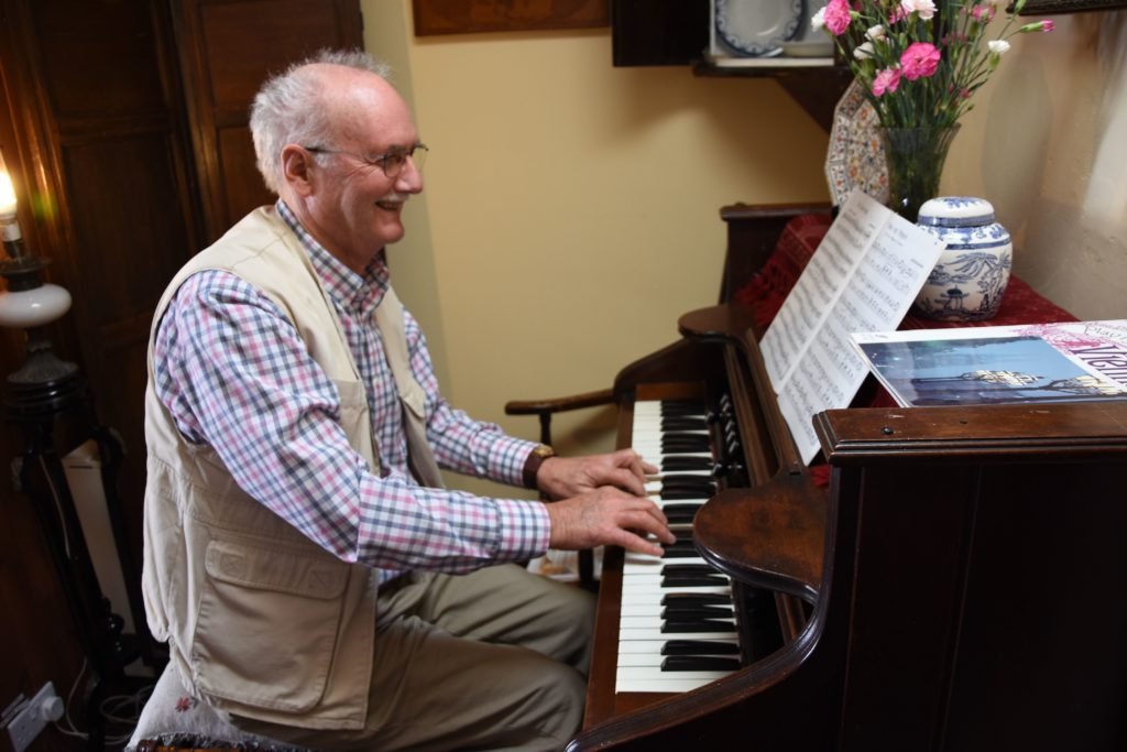 Museum photographer and helping hand, Jim Arnold performs on the organ.