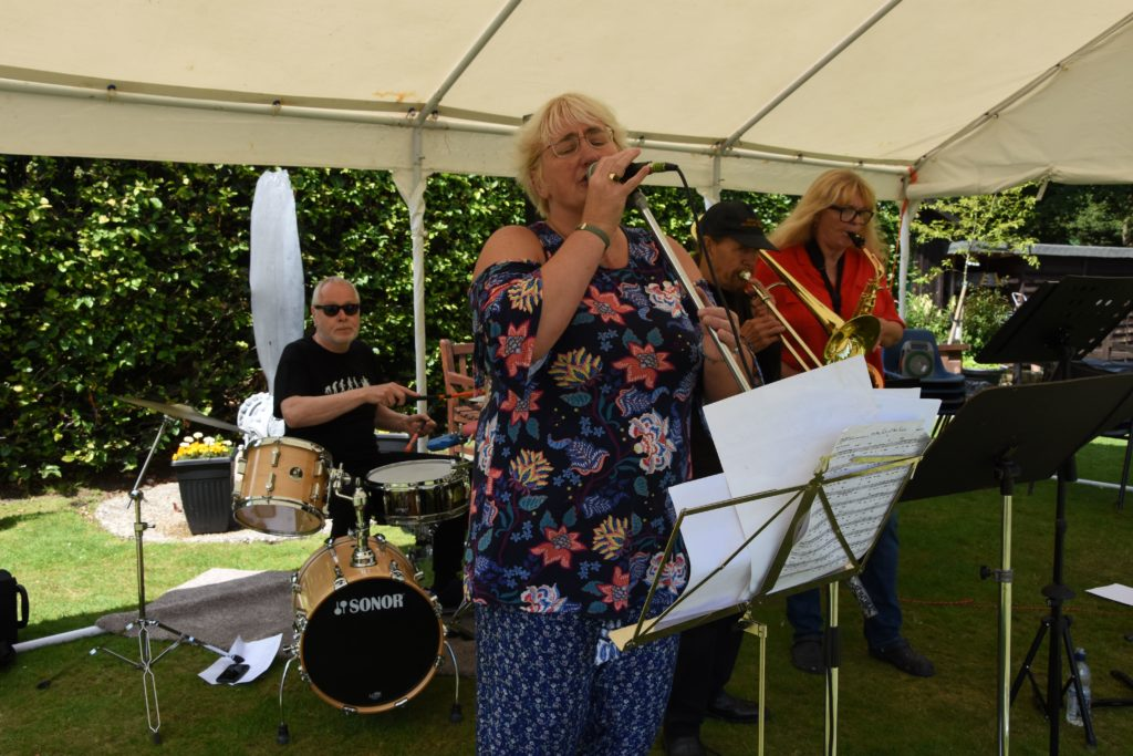 Visitors enjoy the smooth sounds of the Jazz Cafe Band who performed under a marquee in the garden.