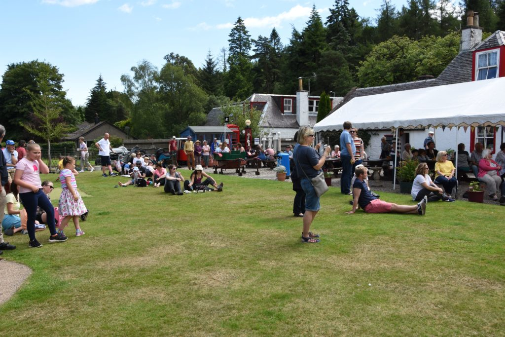The museum lawn becomes an impromptu picnic site where visitors enjoy the live music and refreshments on offer.