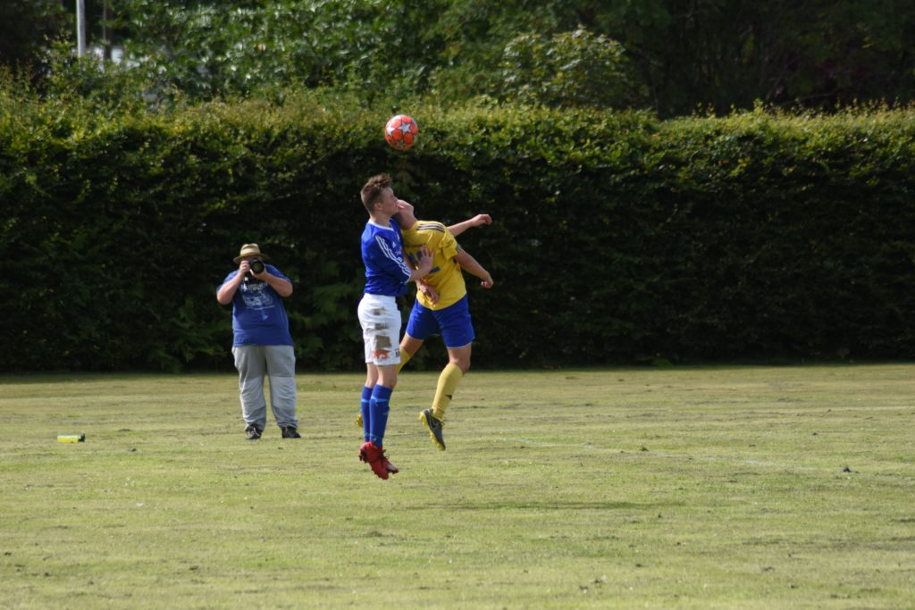 A bruising encounter, players collide as they leap into the air.