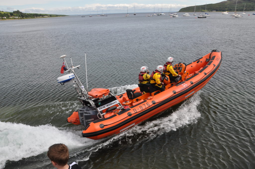 The lifeboat roars off after entering the water.