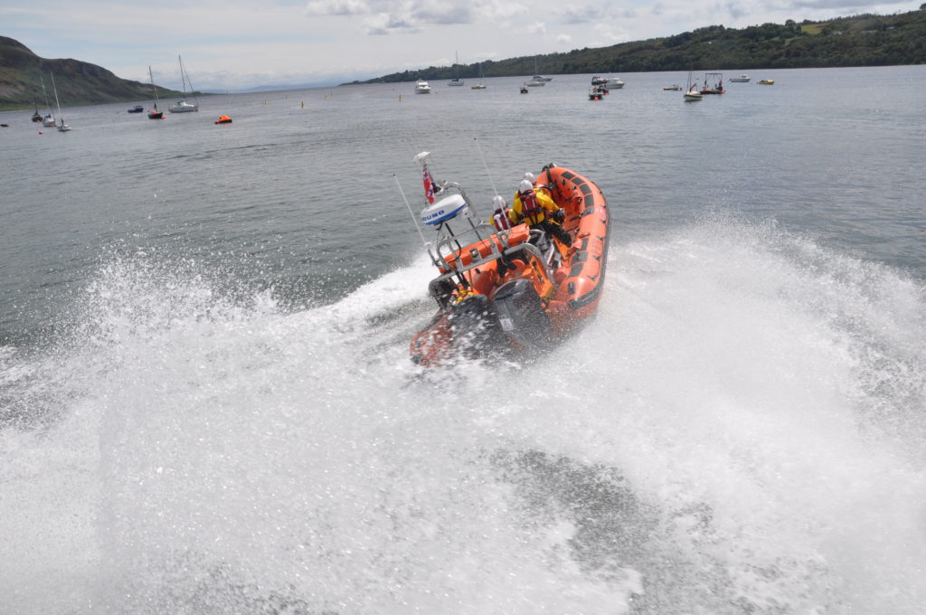 The crowd is splashed by the engines of the lifeboat.