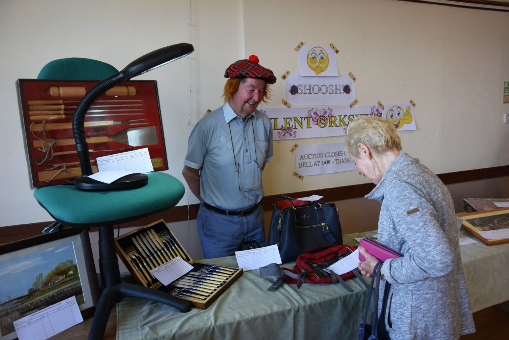 A visitor browses the items up for auction at Leigh Hocking's silent auction stall.