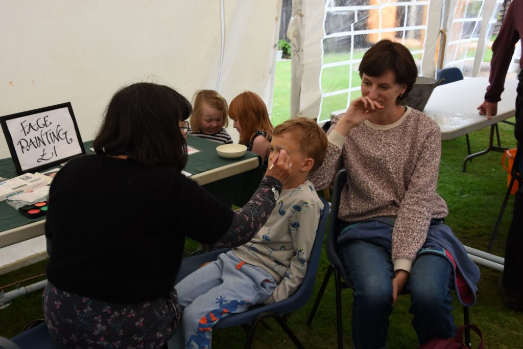 Mum, Claire Gayle, visiting from Essex, watches as her son Eric has his face painted as a minion.
