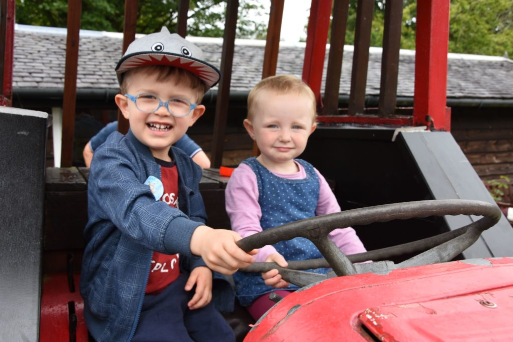 Going for a Sunday drive, two young visitors share the driving seat on Tommy the Tractor.