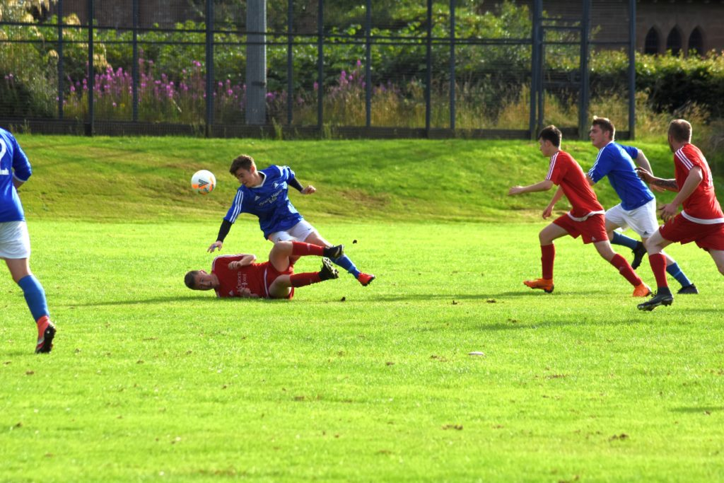 Players from both sides rush for the ball after a tackle trips up two footballers struggling for possession.