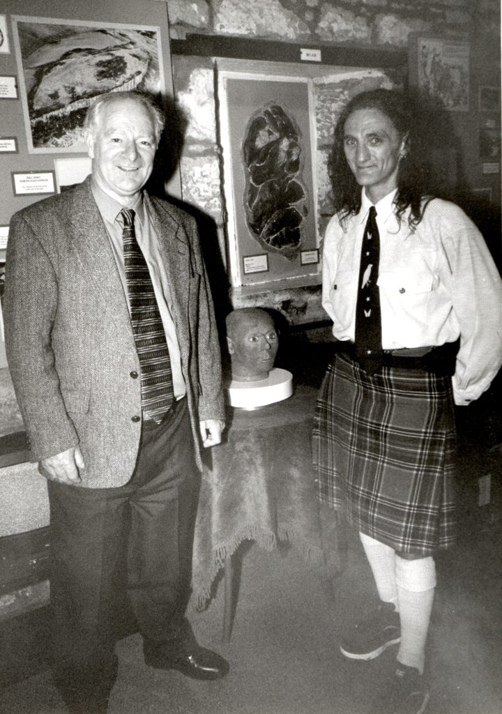 Sculptor David Taylor hands over his model of the Clachaig Man to chairman John Sillars in 1999. The model was created from the skull of a stone age man found at Clachaig above Kilmory in 1900. The original is at the Hunterian Musuem.