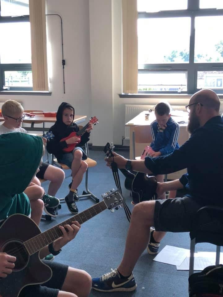 Findlay Napier teaches pupils how to play the ukulele.