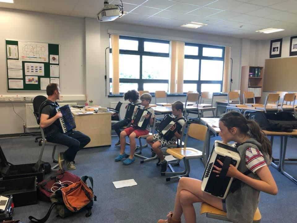 Pupils listen intently to accordion teacher John Somerville.