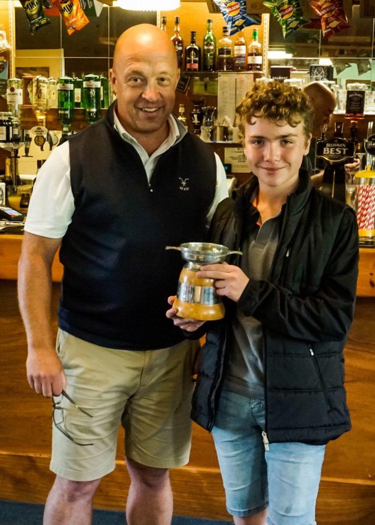 Junior Open champion Cameron Stewart receives his trophy from organiser Alan Foggo.