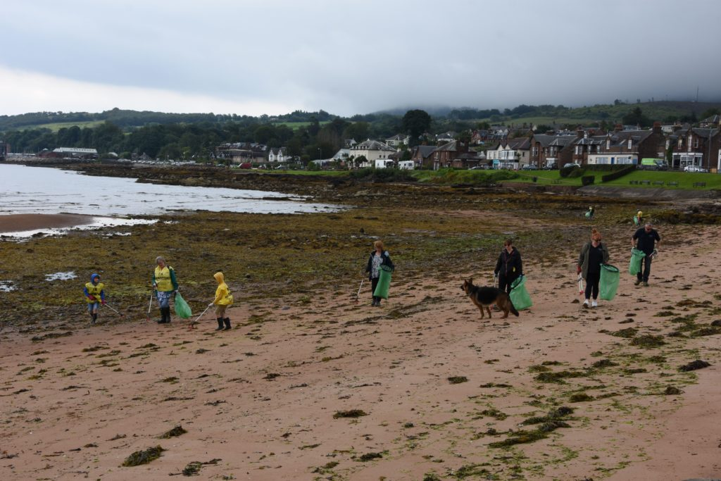 Participants form a line and scour the beach for litter.