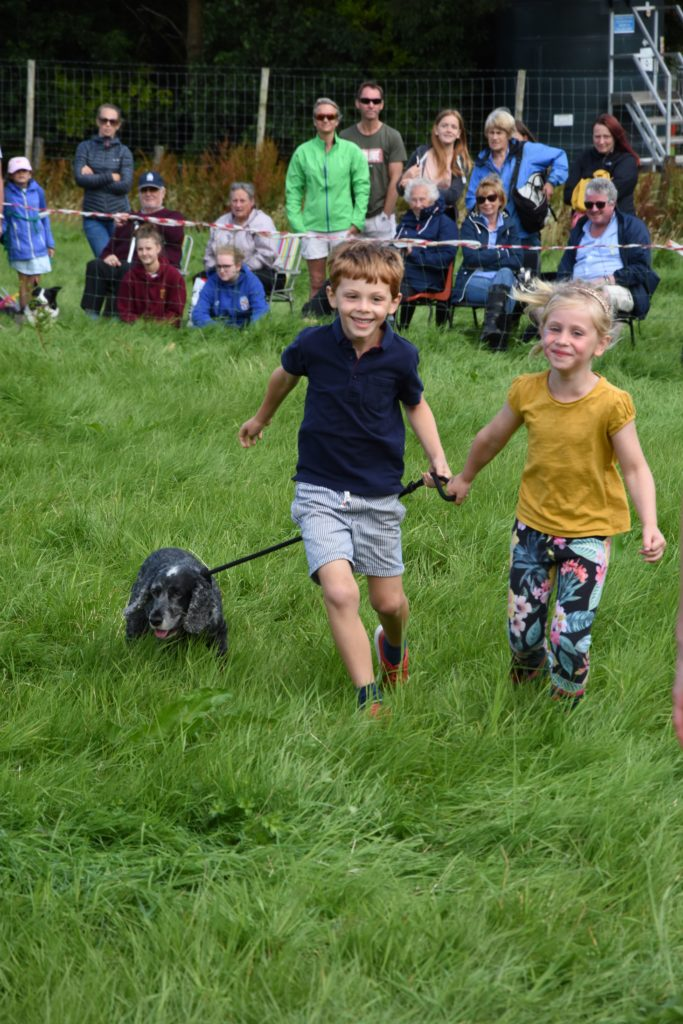 Children parade through the long grass with their dog in the dog judging competition.