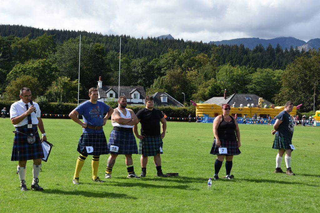 Officiator and previous champion, Alan Pettigrew, and a number of strongmen and woman watch over the heavy events.