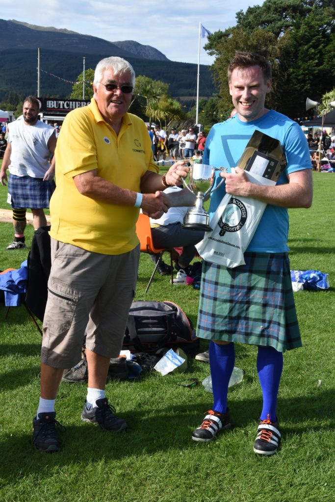 Heavy event champion Paul Dearie receives the Rev James Currie Cup from Charles Currie.