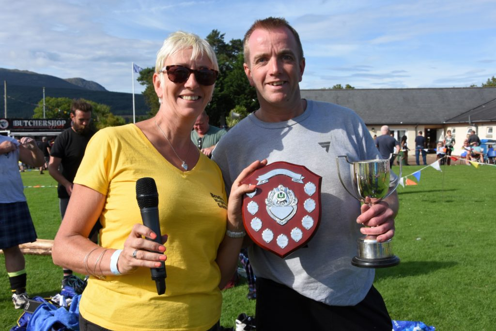 Sheila Gilmore presents Ernie Weir with the William Cook and Sons Trophy for the best caber toss and the Tom Dolan Challenge Trophy for success in seven named events.