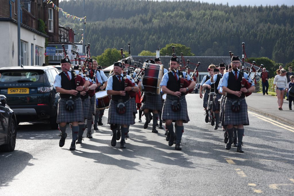 The Isle of Cumbrae Pipe Band march in tight formation down Main road.